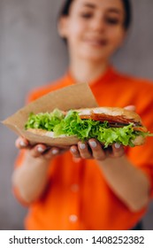 A beautiful, smiling woman in an orange shirt holds a sandwich in her hands. Focus on the sandwich, the background is blurry. ideal concept for advertising fast food cafe with sandwiches