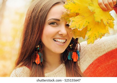 Beautiful smiling woman outdoor portrait, fresh skin and healthy smile, hold maple leaves bunch front of face, dressed in fashion leather earrings