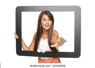 Beautiful smiling woman peeping through tablet frame and stretching her hand attempting to grab something, over white background