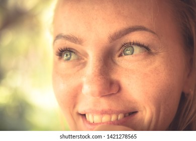 Beautiful smiling woman portrait in warm colors with sunlight on woman face with authentic smile and tan skin