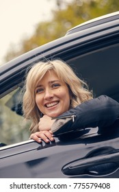beautiful smiling woman posing in car window