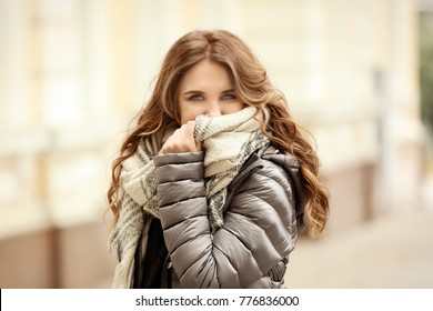 Beautiful smiling woman in puffer jacket outdoors