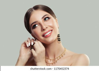 Beautiful smiling woman puting on gold fashion jewelry earrings with black gemstones. Beauty and accessories.