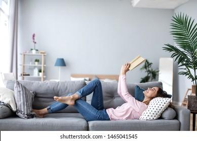 Schöne lächelnde Frau, die ein Buch liest und auf dem Sofa im Wohnzimmer liegt. Viel Spaß zu Hause.