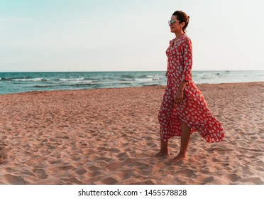 Beautiful smiling woman in red dress and round sunglasses looking to the mediterranean sea at sunset time. Woman on her 30s. Suitable for summer, vations and relaxing time or freedom concepts.