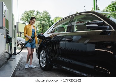 Beautiful smiling woman refueling car on gas station