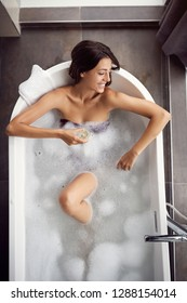 Beautiful smiling woman relaxing in bath with foam top view
