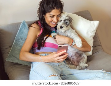 Beautiful  Smiling Woman Relaxing and Hugging her Havanese Dog at Home with Phone in the Hand .Video Call Concept During Covid Isolation