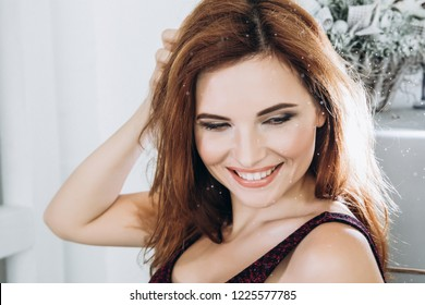 Beautiful smiling woman in ritchen. Manicure nails. Makeup. Red long hair style. Elegant lady in black body frige