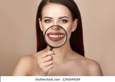 Beautiful smiling woman showing her healthy teeth throug magnifier beige or light brown background