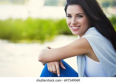 Beautiful smiling woman sitting by the lake.