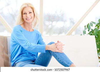 Beautiful smiling woman sitting on sofa and relaxing at home.