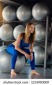 Beautiful smiling woman sitting on fitball in modern gym