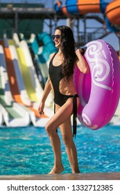 beautiful smiling woman with slim figure in black swimwear holding a swim ring walking near the swimming pool and slides. Summer Vacation. Enjoying suntan. Weekend at resort