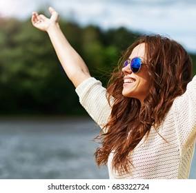 Beautiful smiling woman in sunglasses enjoying freedom outdoor