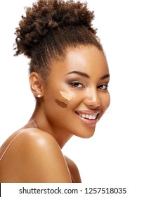 Beautiful smiling woman with tone cream lines on her face. Photo of african american girl with perfect makeup on white background. Skin care concept