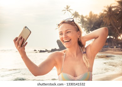 Beautiful smiling woman traveler in bikini on beach making selfie mobile photo on smart phone during beach holidays at beach for social media