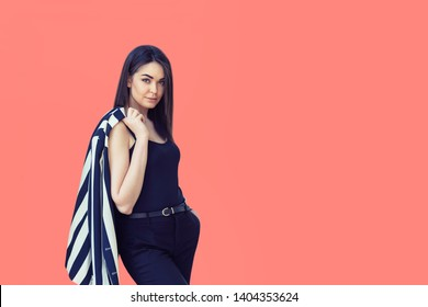 Beautiful smiling woman with trendy fashionable look posing on living coral background – confident young fashion model wearing black and white clothes looking confident at camera