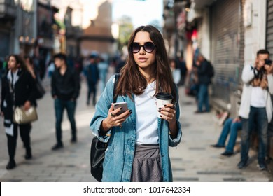 Beautiful smiling woman walking on crowded city street from work with coffee cup and texting on mobile phone