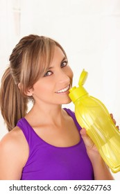 Beautiful smiling woman wearing a purple t-shirt and drinking a yellow bottle of water