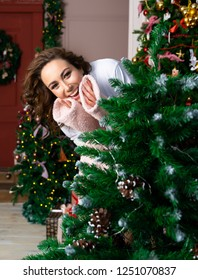 Beautiful smiling woman wearing warm fluffy robes peeks out from behind a Christmas tree, decorated with garlands. Copy space.