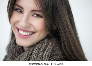Beautiful smiling woman wearing a warm woolen scarf.