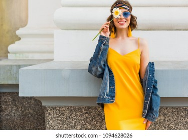 beautiful smiling woman in yellow stylish dress wearing denim jacket, holding flower, trendy outfit, hippie indie style, spring summer fashion trend, blue sunglasses, street fashion, smiling, happy