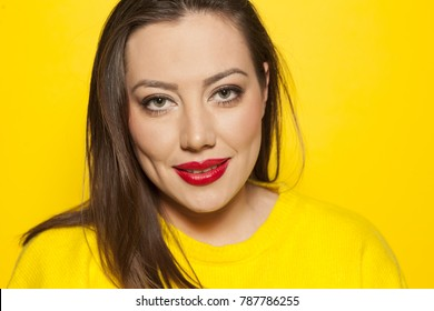 beautiful smiling woman in a yellow sweater on a yellow background