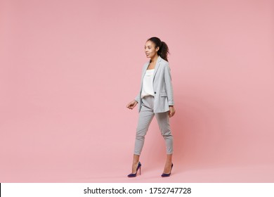 Beautiful smiling young african american business woman in grey suit, white shirt posing isolated on pink background. Achievement career wealth business concept. Mock up copy space. Looking aside
