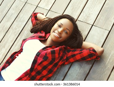 Beautiful smiling young african woman relaxed on wooden floor with hands behind head, wearing a red checkered shirt, top view