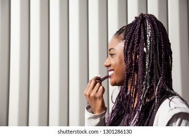 Beautiful, smiling and young afro woman with braids, painting her lips with a lipstick