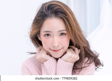 Beautiful Smiling Young Asian Woman with Clean, Fresh, Glow, and pefect Skin in pink sweater, winter concept. Happy, healthy, cheerful, relaxing girl in white living room.