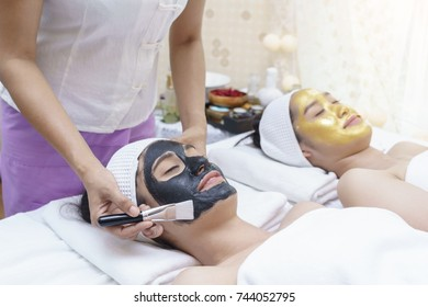 Beautiful smiling young Asian women having mud mask and high quality authentic pure gold facial mask  , lying on massage table in spa salon