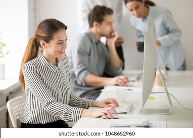 Beautiful smiling young businesswoman working on desktop computer in office typing message to client or writing emails, elegant female employee using pc sitting at workplace looking at monitor