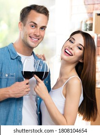 Beautiful smiling young couple drinking redwine, at home. Caucasian models with red wine glasses in love concept. Happy man and woman posing together indoors. 14 february, valentine holiday, Valentin