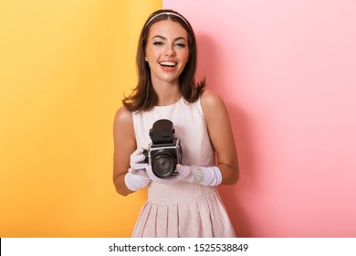 Beautiful smiling young elegant brunette woman wearing dress and gloves standing isolated over double color background, holding retro photo camera