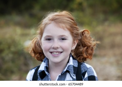Beautiful smiling young girl with red hair outdoors in Autumn season