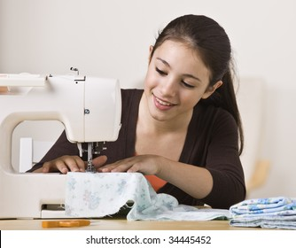 A beautiful, smiling young girl sewing on a sewing machine.  Horizontally framed shot.