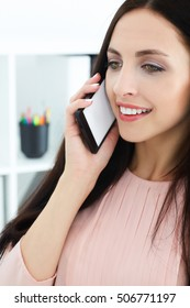 Beautiful smiling young girl talking on the mobile phone closeup. Mobile advertising.
