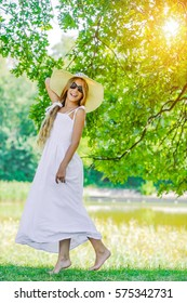 Beautiful smiling young girl in white dress, wearing sunglasses and straw hat, background of green summer park.