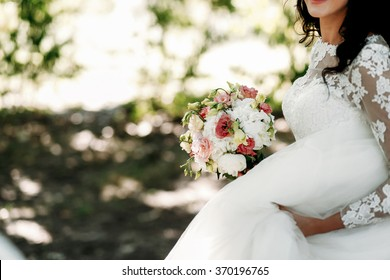 Beautiful smiling young happy brunette bride in a white dress with wedding bouquet and luxury veil n the summer green park