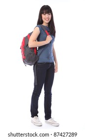 Beautiful smiling young Japanese teenager high school student girl wearing blue denim jeans and t shirt, school backpack over shoulder.
