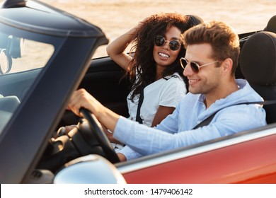 Beautiful smiling young multiethnic couple riding in a convertible