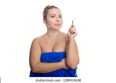 Beautiful smiling young plus size woman isolated on white background wrapped in a blue towel, holds a razor. The concept of beauty and personal care.