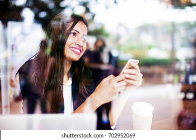 A beautiful smiling young professional Indian woman browsing her phone while having a beverage