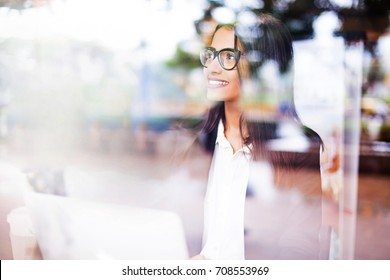 a beautiful smiling young professional beautiful Indian woman wearing a suit and spectacles working on a laptop. View through the window