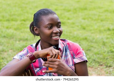 A beautiful smiling young Ugandan woman with headphones around her neck