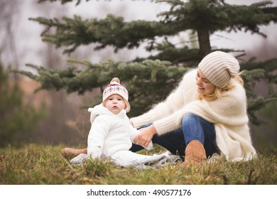 Beautiful smiling young woman with adorable baby boy sitting on the grass near a nice fir tree. Mother with child walking in the park on a cold day. Motherhood and lifestyle concept
