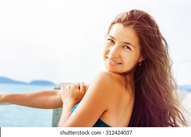 Beautiful Smiling Young Woman with Black Long Hair Looks at Camera. Summer day on a Pier