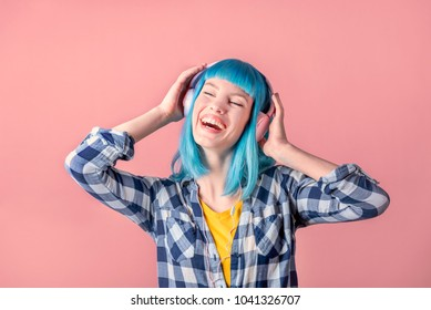 Beautiful smiling young woman with blue color dyed hair with pink headphones listening to music and dance in front of pastel studio background.